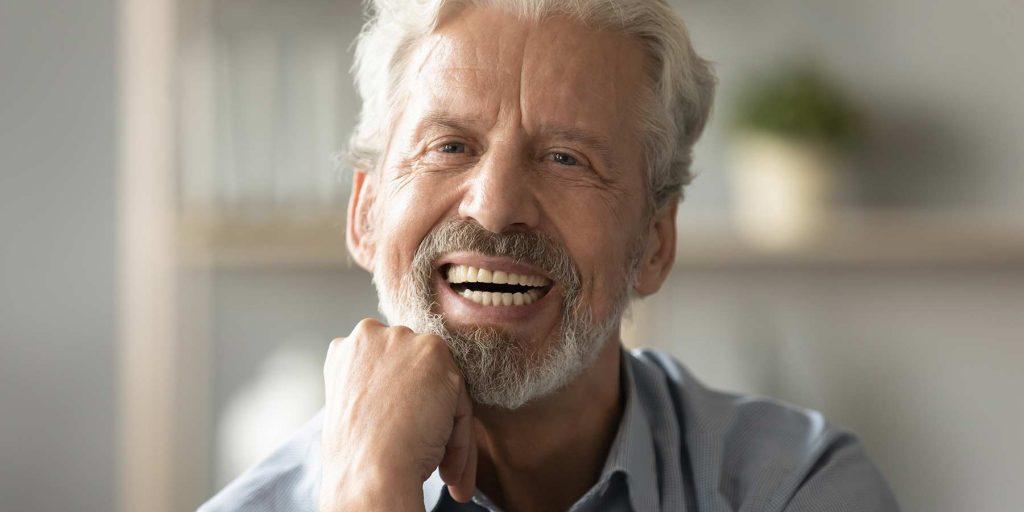 تصویری یک مرد درحالی که دندان مصنوعی دارد در حال خندیدن است